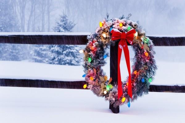 Corona de Navidad iluminada colgada de una valla bajo la nieve