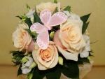 Una mariposa rosa decorando un ramo de rosas