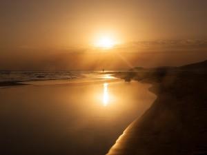 Un hombre caminando en una playa bajo un dorado atardecer