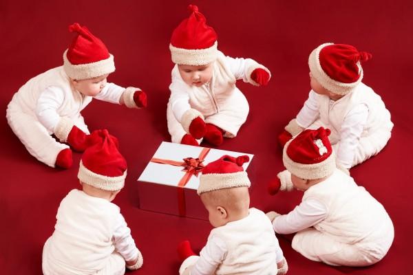 Bebés con gorros de Papá Noel alrededor de un regalo