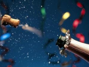 Destapando una botella de champán para festejar la llegada del Nuevo Año 2015