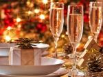 Copas de champán y regalos en la mesa de Navidad