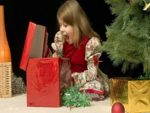 Postal: Asombro y sorpresa de una niña al abrir su regalo de Navidad