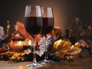 Dos copas con vino tinto y una decoración otoñal