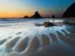Una gran playa con formaciones rocosas
