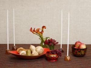Velas largas y blancas sobre una mesa con frutas y flores