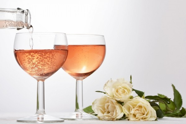 Sirviendo champán en copas junto a un ramo de rosas blancas