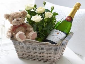 Cesta con champán, rosas y un osito de peluche