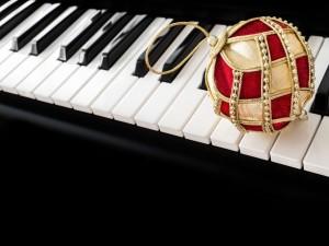 Postal: Bola dorada y roja sobre las teclas de un piano