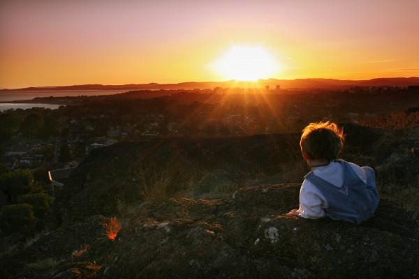 Un niño sobre las rocas admirando el amanecer