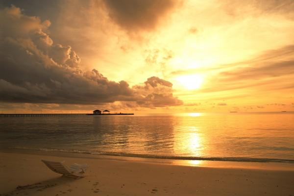 Silla en una playa al atardecer