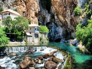Postal: Maravillosa aldea junto a unas rocas y un río