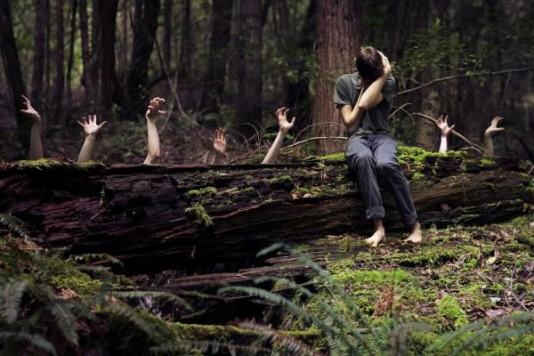 Manos espeluznantes detrás de un tronco