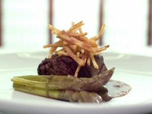 Carne en salsa acompañada de espárragos y patatas fritas