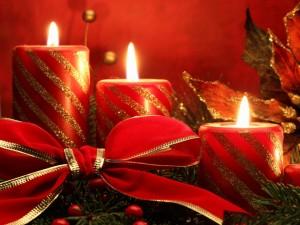 Velas rojas con un gran moño para celebrar las fiestas de Navidad