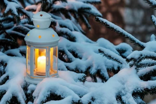 Farol con una vela encendida sobre una rama con nieve
