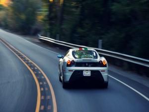 Postal: Ferrari circulando por una carretera