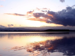 Postal: El agua de un lago brillando al amanecer