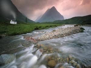 Casa blanca junto al río y las montañas