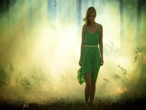 Joven caminando en el bosque con un vestido verde