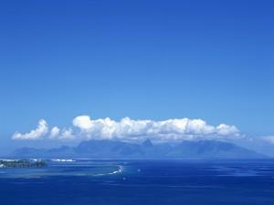 Postal: Vista de un mar, montañas y nubes