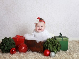 Postal: Una bebé entre regalos navideños