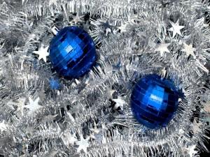 Postal: Dos bolas azules sobre espumillón de Navidad