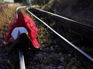 Mujer tumbada sobre la vía de un tren
