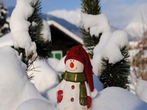 Postal: Figura de un muñeco de nieve entre blanca nieve