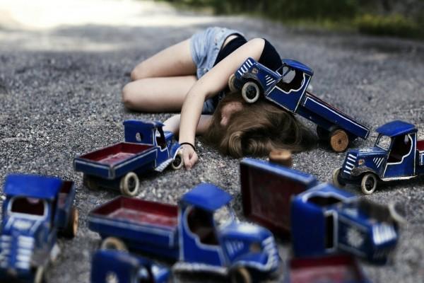 Mujer caída en el suelo entre camionetas
