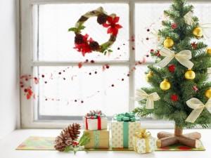 Árbol de Navidad y regalos junto a una ventana