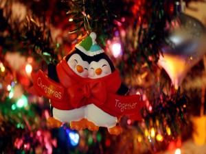 Dos simpáticos pingüinos colgados en el árbol de Navidad