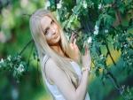 Mujer junto a un árbol en flor