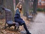 Mujer sobre un banco en otoño