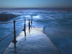 Postal: Pasarela de hormigón inundada por el mar