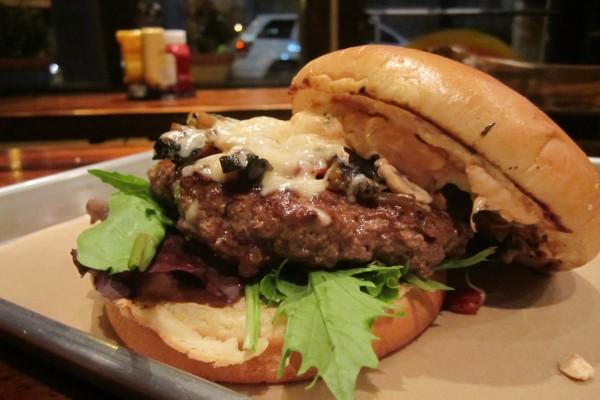 Verduras y queso sobre la carne de una hamburguesa