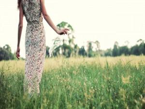 Postal: Mujer con un vestido de flores caminando por el campo