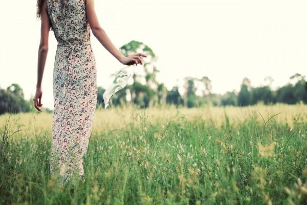 Mujer con un vestido de flores caminando por el campo