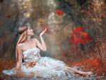 Bella mujer entre hojas de otoño