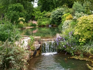 Postal: Cascada en un jardín rodeada de arbustos, árboles y magníficas flores
