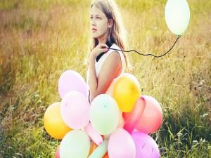Postal: Una chica con varios globos en el campo