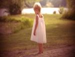 Una niña pequeña descalza sobre la tierra