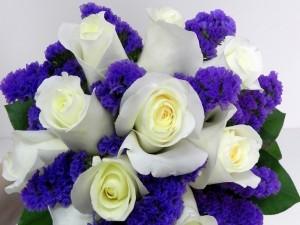 Un delicado ramo con rosas blancas y pequeñas flores color púrpura