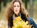 Una mujer con hojas otoñales