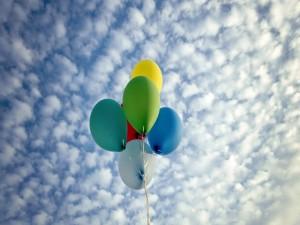 Postal: Globos de colores volando hacia las nubes