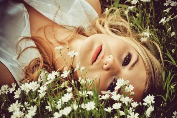 Mujer tumbada sobre las florecillas blancas