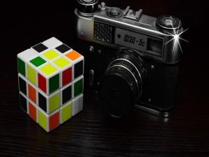 Postal: Cámara de fotos junto a un cubo de rubik