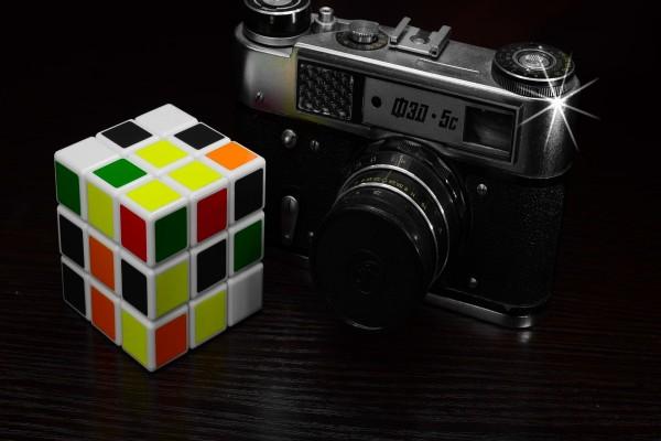 Cámara de fotos junto a un cubo de rubik