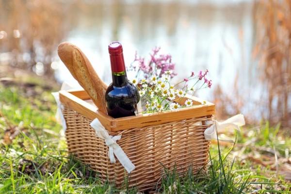 Vino, baguette y flores en una canasta