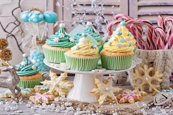 Cupcakes en una mesa con otros dulces para comer en los días festivos